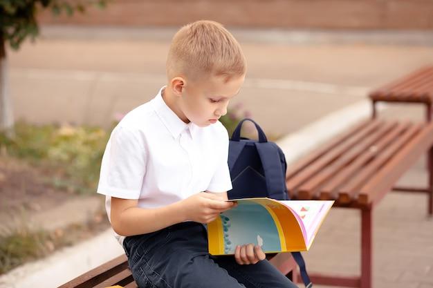 벤치에 앉아서 교과서를 읽는 제복을 입은 남학생.