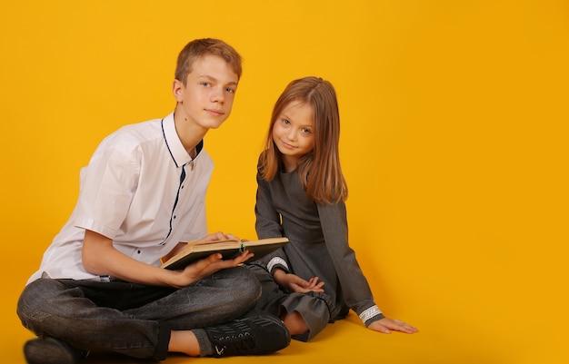 Школьник в белой рубашке и серых брюках сидит со своей сестрой школьница читает книгу