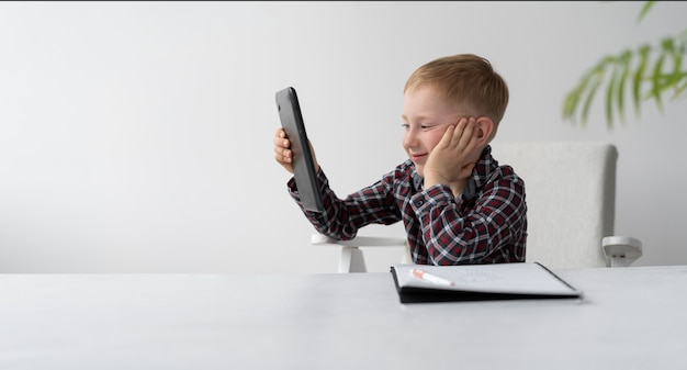 A schoolboy is doing quarantine homework at home. distance learning child. the boy is sitting in front of the table. on the table is a large notebook.. skype lessons. online education at