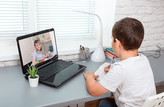 Schoolboy is having video chat with teacher on laptop computer at home.