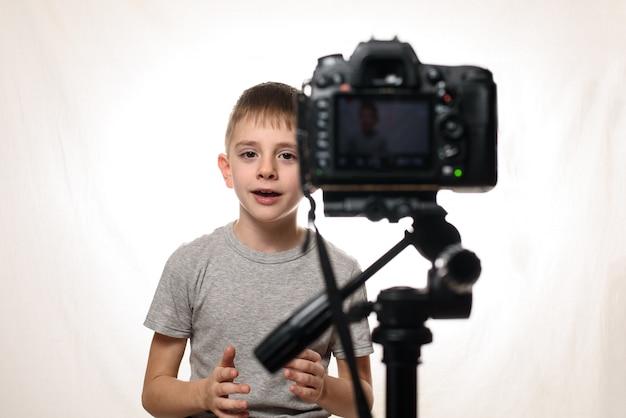 男子学生はビデオカメラで何かを言っています。若いビデオブロガー。白い