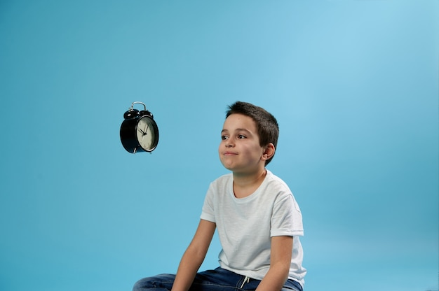 Schoolboy looking at a flying alarm clock while sitting on blue surface