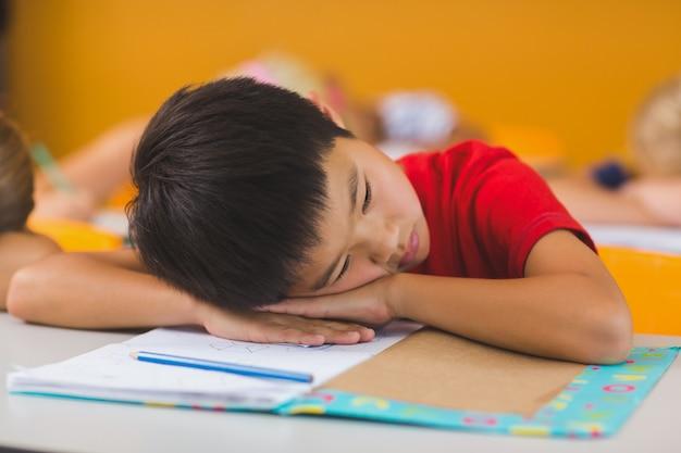 教室の机の上に横たわる少年
