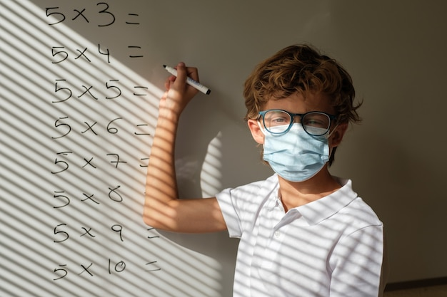 Schoolboy in mask writing on whiteboard during math lesson