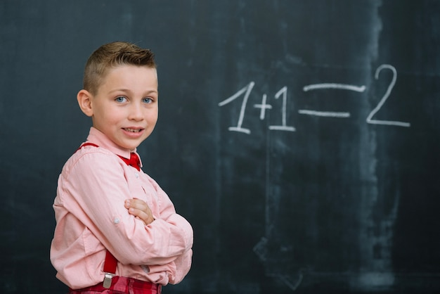 Schoolboy on math lesson with arms crossed