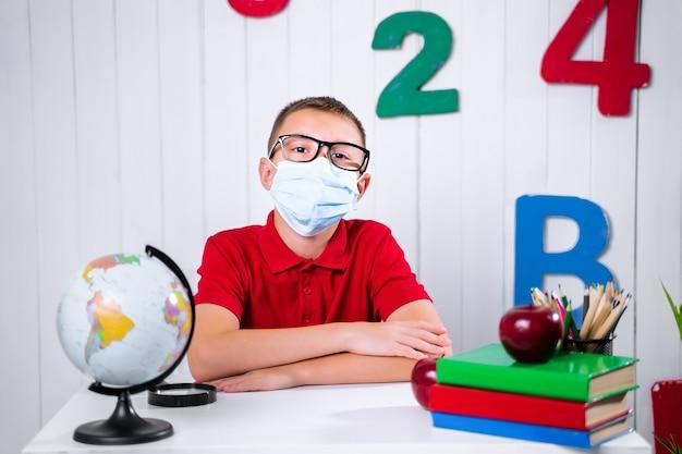 A schoolboy in medikal mask at a desk.