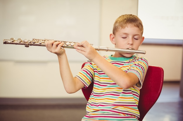 Schoolboy playing flute in classroom