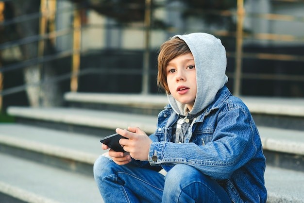 Schoolboy playing game on smartphone after school. technology, lifestyle, leisure. children addicted online games and videos.