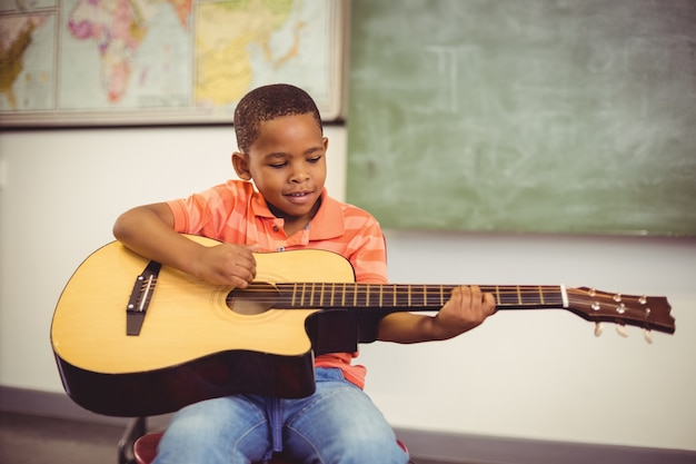 Schoolboy playing guitar in classroom