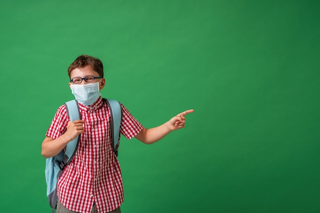Schoolboy in protective mask, standing against background of a green board