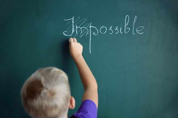 Schoolboy putting a cross over word impossible on blackboard