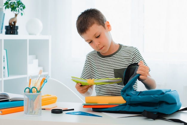 Schoolboy putting school stationery into backpack at table indoors at home white room. preparation for school, homework