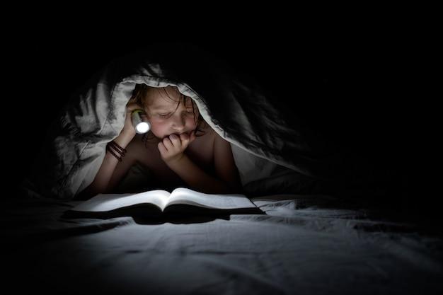 Schoolboy reading under blanket at night.
