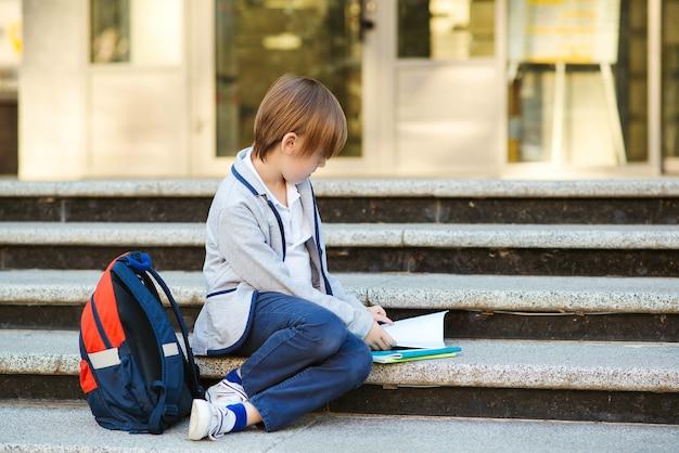 Школьник читает книгу, сидя на лестнице
