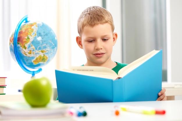 Schoolboy reading a heavy blue book