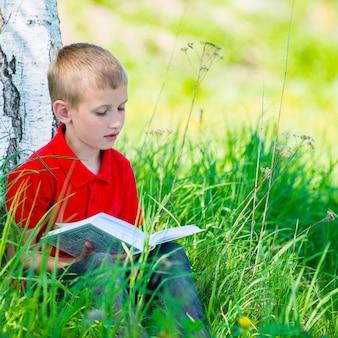 Школьник читает книгу на природе