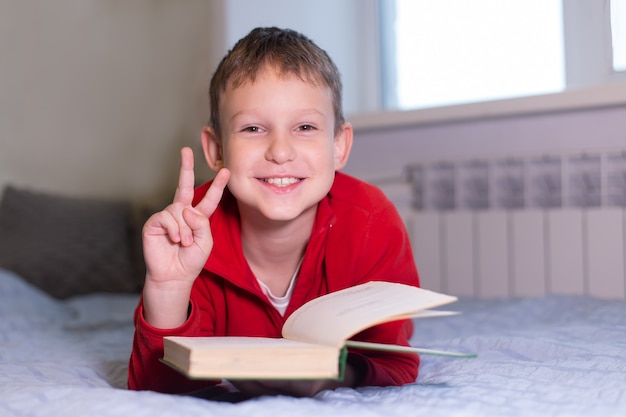 The schoolboy reads book at home, distance learning