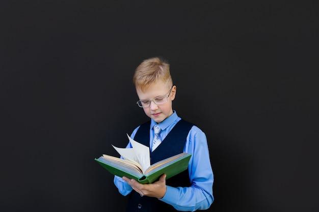 The schoolboy reads near school board