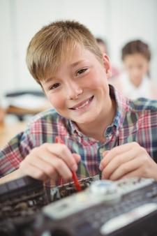 教室でプリンターを修理する少年