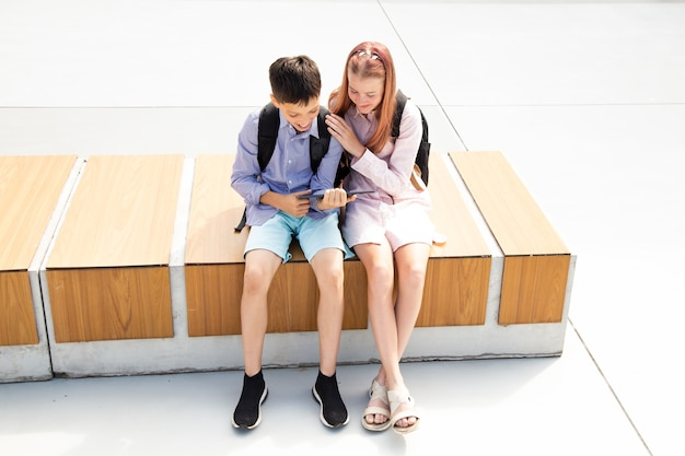 Schoolboy schoolgirl teenagers laugh have fun after lessons sitting on wooden bench in schoolyard, concrete background use tablet, concept of online education, modern technologies in kids life
