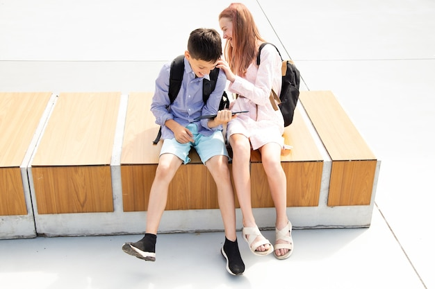 Schoolboy schoolgirl teenagers laugh have fun after lessons sitting on wooden bench in schoolyard, concrete background use tablet, concept of online education, modern technologies in life of children