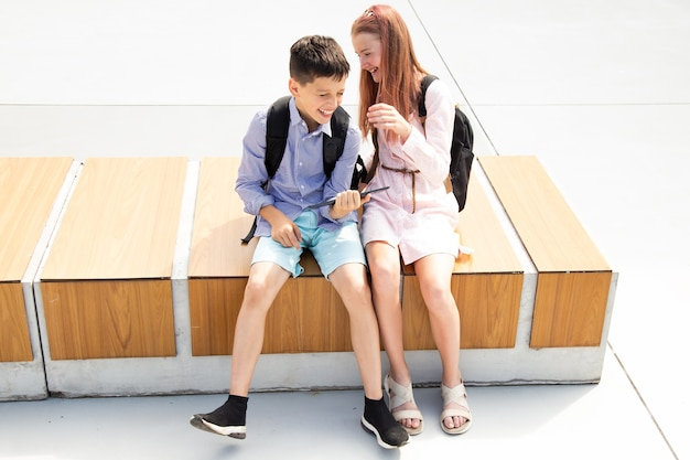 Schoolboy and schoolgirl teenagers laughing after lessons while sitting on wooden bench in the schoolyard, concrete background, online education concept
