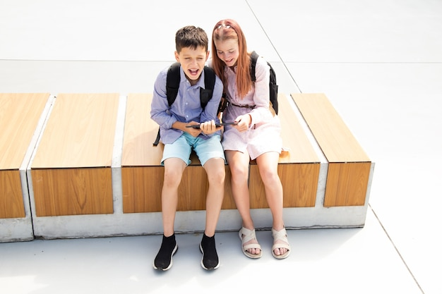 Schoolboy and schoolgirl teenagers receive online lesson while sitting on a wooden bench in schoolyard, concrete background, online education concept