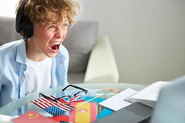 ノートパソコンを見て、ドンの宿題の時間の間にゲームをしている男子生徒の悲鳴