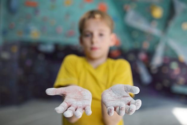 ジムで練習を登っている間彼の手を示す少年はタルクで覆われて