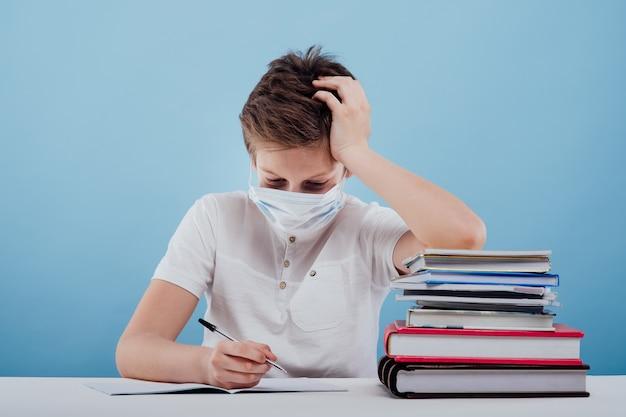 의료용 마스크를 쓰고 탁자에 앉아 있는 남학생은 탁자에 앉아 있는 것이 지겹다는 것을 배운다...