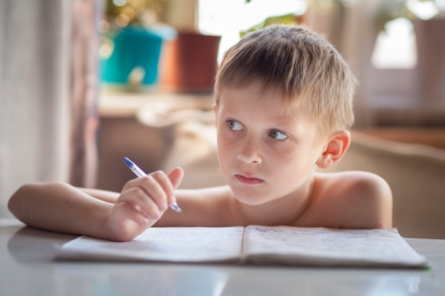 Schoolboy sits at a table thoughtfully and does homework