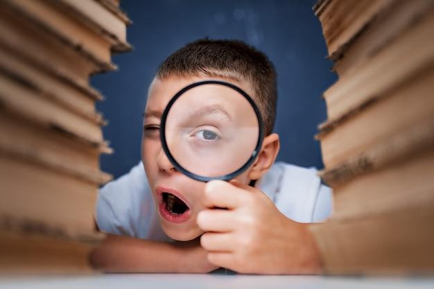 Школьник сидит между двумя стопками книг и смотрит в камеру через увеличительное стекло.