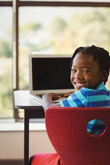 Schoolboy sitting on chair and using laptop at school