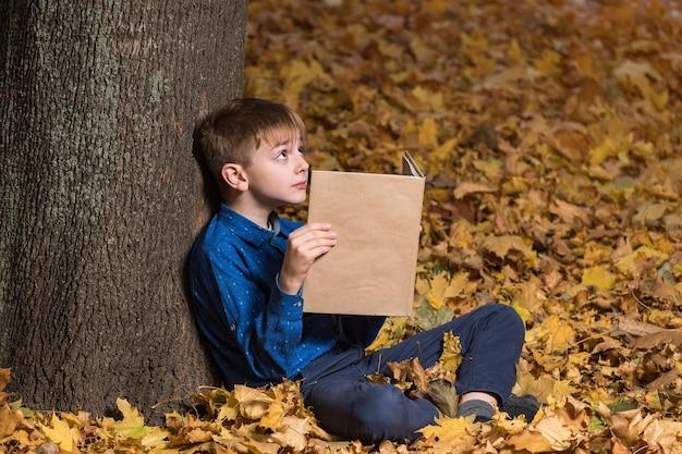 Школьник сидит возле дерева в опавших желтых листьях и держит книгу. копировать пространство. макет.