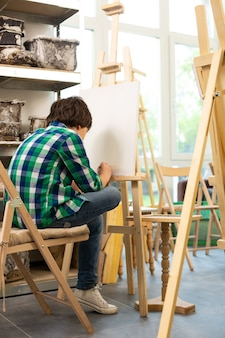 Schoolboy sitting near window and painting in art school