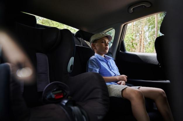 車での安全な旅行のためにngを締める前に安全なチャイルドシートに座っている男子生徒