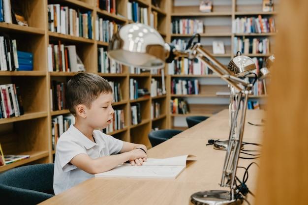 학교에서 테이블에 앉아 책을 읽고 있는 남학생 숙제 준비