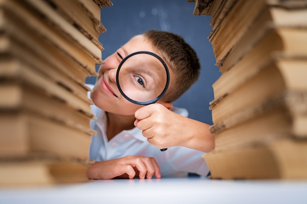 Schoolboy sitting between two piles of books looking at camera through the magnifying glass.