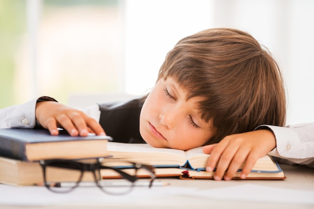 Schoolboy sleeping. cute little boy sleeping while sitting at the table and leaning his face at the desk