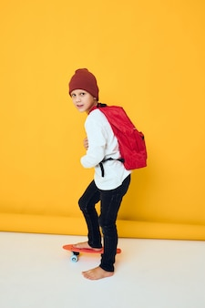 A schoolboy stands on a skateboard on a yellow background
