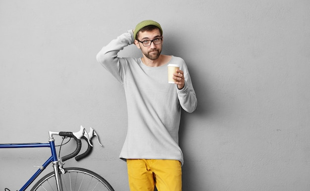 Schoolboy stratching his head while keeping takeaway coffee, trying to remember what he should take in his bag, standing near grey wall and bicycle. male going on picnic by bike. people and rest