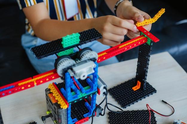 ロボット工学のクラスで男子生徒が勉強し、ロボットコンストラクターを組み立てます。