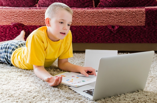 Schoolboy studying at home with laptop