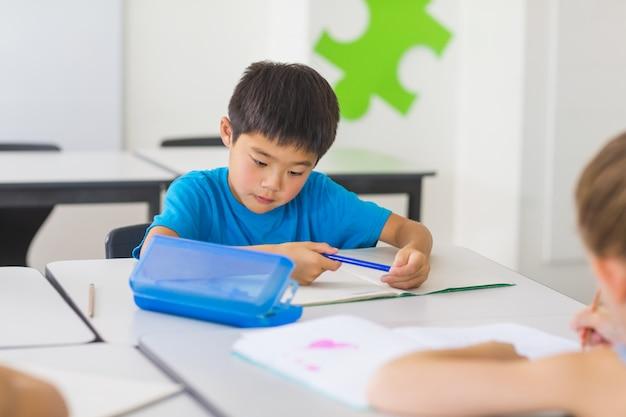 教室で勉強している少年