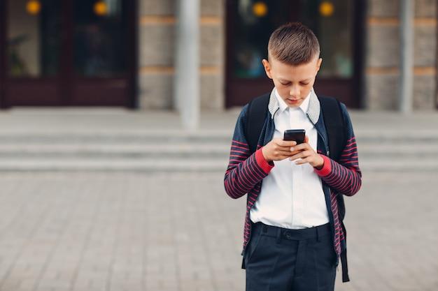 Школьник подросток мальчик с мобильным телефоном, стоя в школе на фоне