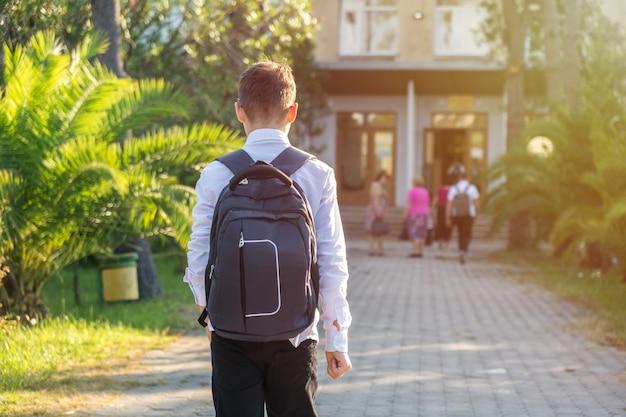 Schoolboy in uniform goes to school, education.
