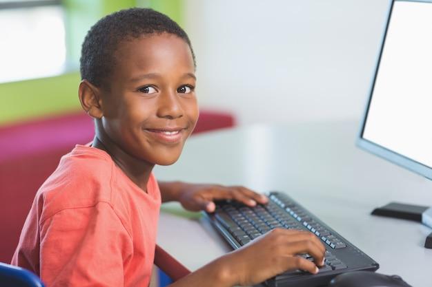 教室でコンピューターを使用している少年