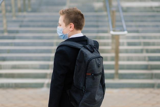 남학생은 도시에서 보호 마스크를 착용하고 학교를 나갑니다.