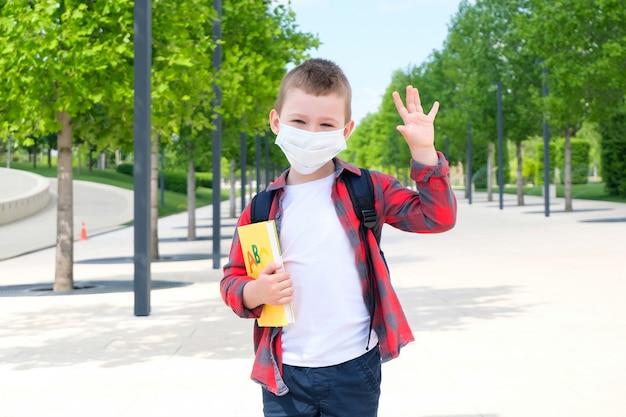 Школьник в защитной маске от вируса с учебником в руках стоит на улице по дороге в школу. обратно в школу