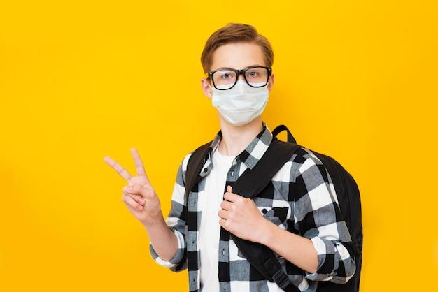 孤立した黄色の背景にバックパックと医療フェイスマスクを身に着けている男子生徒